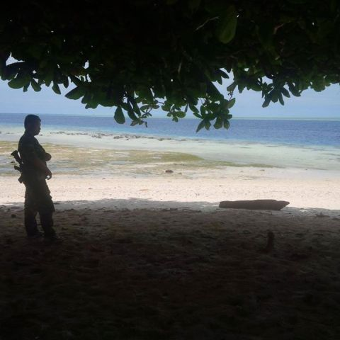 An Army personnel stands guard at Siamil island and can only watch boats go by