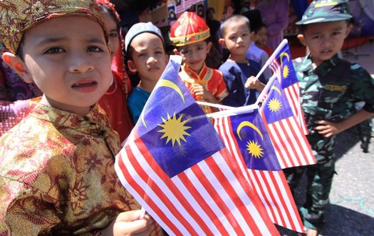 Children in different costumes holding the Malaysia flag - BERNAMA