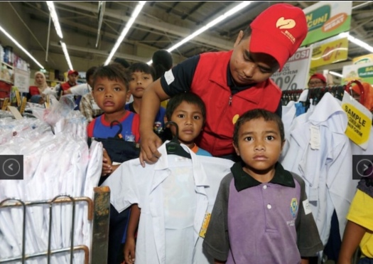 Forest City staff assisting Orang Asli children to choose their school uniform at the Giant Hypermarket in Tampoi (pic courtesy of NSTP/Hairul Anuar Rahim)